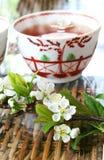 Tea and Blossom. On rattan table Stock Photos