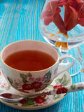 Tea on a blue background. Tea, porcelain cup, blue background, biscuits, red flowers Stock Photography
