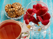 Tea on a blue background. Tea, porcelain cup, blue background, biscuits, red flowers Royalty Free Stock Image