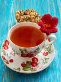 Tea on a blue background. Tea, porcelain cup, blue background, biscuits, red flowers Stock Photos