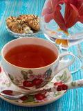 Tea on a blue background. Tea, porcelain cup, blue background, biscuits, red flowers Royalty Free Stock Photography