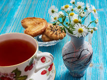 Tea on a blue background. Porcelain cup with tea on a blue table and chamomile Stock Photo