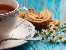 Tea on a blue background. Porcelain cup with tea on a blue table and chamomile Stock Images