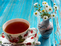 Tea on a blue background. Tea in a porcelain dish on a blue table and chamomile Stock Photos