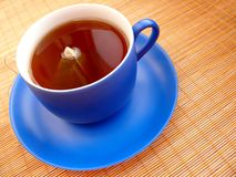 Tea in blue cup. Cup of tea on bamboo mat royalty free stock photos