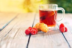 Tea boiled in a bag of raspberries and biscuits on a wooden table royalty free stock photography