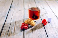 Tea boiled in a bag of raspberries and biscuits on a wooden table stock photo