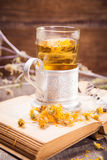Tea on book. Tea on old book with yellow flowers in studio Stock Photography