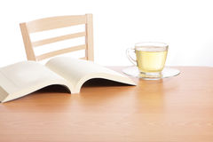 Tea and book on wood table Stock Photos
