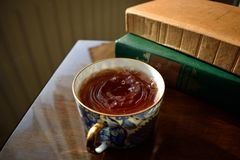 Tea and books. A cup of tea in white and blue porcelain with old books Royalty Free Stock Photos