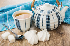 Tea in bowl, striped teapot, meringue, lumpy sugar and teaspoon Stock Image