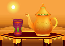 Tea Break. Golden arabic teapot and a glass on a table Stock Photos