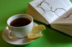 Tea Break. Cup of black tea with lemon and book with reading glasses Royalty Free Stock Photography