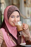 Tea break. Pretty young Asian Muslim woman with lovely smiles having lunch at coffee shop Stock Photography