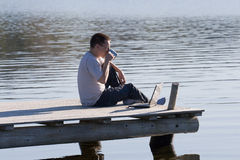 Tea break. Man sitting on pier above lake water with laptop and drinking cup of tea at sunny summer day Stock Photography