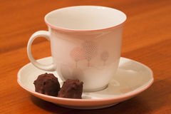 Tea Break with Cacao Praline. A pottery tea cup with trees hand-painted and a delicious chocolate praline with cocoa beans, in a parquet background Royalty Free Stock Image