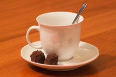 Tea Break with Cacao Praline. A pottery tea cup with trees hand-painted, a spoon and a delicious chocolate praline with cocoa beans, in a parquet background Stock Image