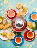 Tea break with cups, flowers, cakes and tea pot on light blue background Royalty Free Stock Photos