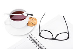 Tea break. Glasses and notebook with a cup of tea and cookie isolated on white background Royalty Free Stock Images