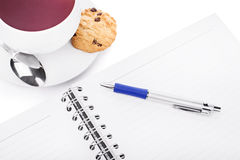 Tea break 1. Pen and notebook with a cup of tea, chocolate chip cookie and a small spoon isolated on white background Stock Images