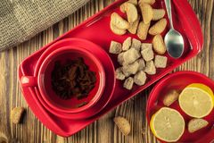 Tea break. tea in a red ceramic dish on a tray with cane sugar, crackers and lemon on a wooden background. top view. Tea break. Tea in a red ceramic cup on a stock photos