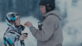 Tea break during skiing on the mountain. Man and woman drinking tea at a ski resort stock footage