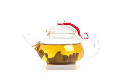 Tea is brewed in a transparent tea pot on white background Royalty Free Stock Photo