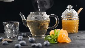 Tea brewing ceremony. Green Chinese Tea Flower in Glass Teapot on wooden Background. blueberry, glass can with honey. Pouring boiled water. Slow motion. hd stock video