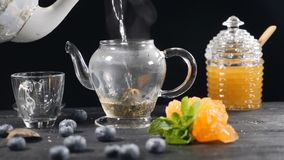 Tea brewing. Green Chinese Tea Flower in Glass Teapot on wooden Background. blueberry, glass can with honey. Pouring. Boiled water. Slow motion. hd stock video