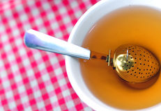 Tea brewing spoon in a cup Royalty Free Stock Image
