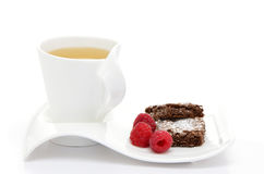 Tea with brownies and raspberries. Fresh hot herbal tea with brownies and raspberries on white background Stock Photos