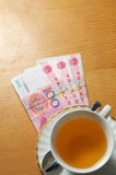 Tea bussiness. A cup of tea and some rmb on the office desk Stock Image