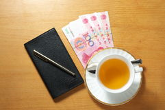 Tea bussiness. A cup of tea and some rmb on the office desk Royalty Free Stock Image