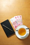 Tea bussiness. A cup of tea and some rmb on the office desk Royalty Free Stock Photos