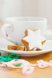 Tea with cake and Christmas decoration. Table served to tea drinking. White cup of tea, star cake and Christmas decoration on the wooden table Stock Photography