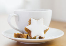 Tea with cake and Christmas decoration. Table served to tea drinking. White cup of tea, star cake and Christmas decoration on the wooden table Royalty Free Stock Image