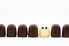 Tea cake - dark and white choco softies with googly eyes on white background. Tea cake line - dark and white choco softies with googly eyes on white background Royalty Free Stock Image