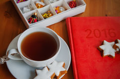 Tea with cake , diary and Christmas decoration. Table served to tea drinking. White cup of tea, star cake, diary for 2016 year  and Christmas decoration on the Royalty Free Stock Photos