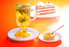 Tea and cake. Fresh tea with mint and lemon slices royalty free stock photography