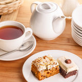Tea and cake slices. A cup of steaming tea with two pieces of cake on plate surrounded by various kitchenware on wooden plate Royalty Free Stock Photos
