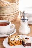 Tea and cake slices. A cup of steaming tea with two pieces of cake on plate surrounded by various kitchenware on wooden plate Royalty Free Stock Image