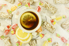 Tea with cakes, candies and lemon. Royalty Free Stock Image
