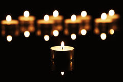 Tea candle in front of many tea candles Royalty Free Stock Images