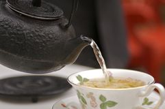 Tea Ceremony. Green tea being poured from iron tea pot into China cup stock photography