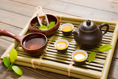 Tea ceremony. Teapot,tea cup and tea leaves on a bamboo mat Stock Photos