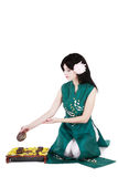 Tea ceremony. Brunette in green asian costume arranging tea ceremony Stock Photo