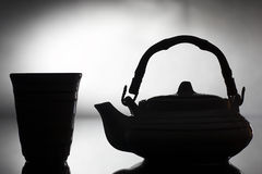 Tea ceremony. Silhouette teapot and cup royalty free stock photography