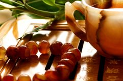 Tea ceremony. China. Onyx cup on the table. Near bamboo and beads of carnelian Stock Image