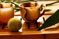 Tea ceremony. China. Onyx cup on the table. Near bamboo and massage ball Stock Photos