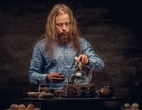 Tea ceremony concept. Portrait of a redhead hipster male with long hair and full beard dressed in a blue shirt royalty free stock photo